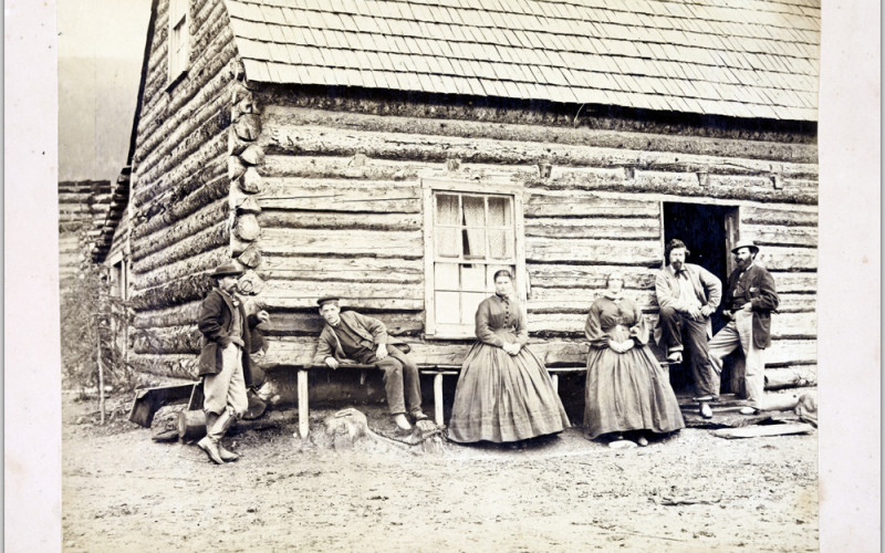 family standing next to log cabin